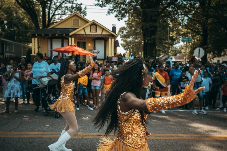 Majorettes wearing gold outfits dance down a street during a parade.