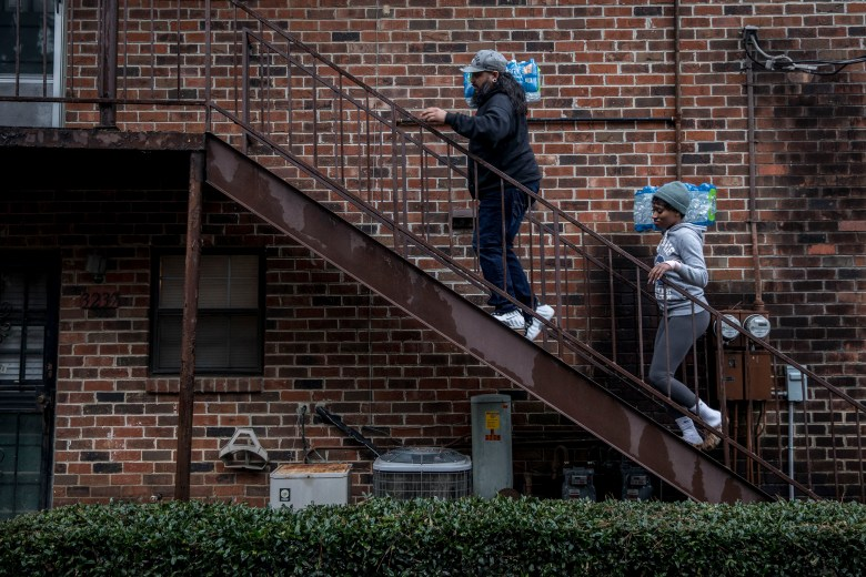 A man and woman walk up stairs alongside a brick building to distribute water to community members.