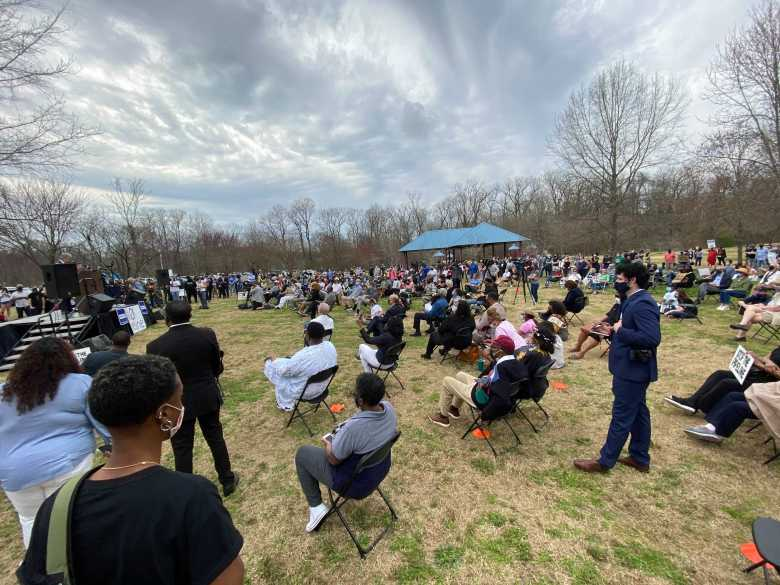 A photo of large crowd of people seated on the lawn of Mitchell High School