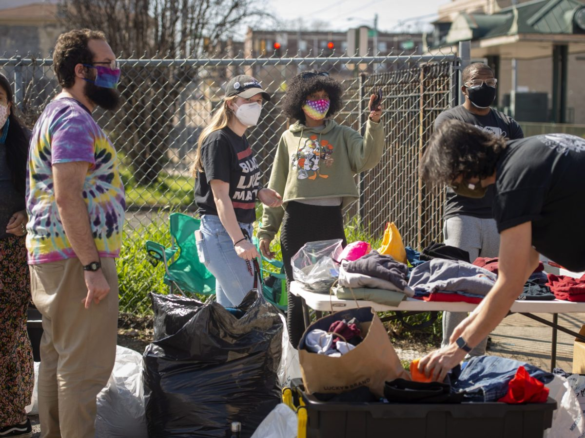 """Several people stand alongside folding tables as they arrange clothes for a """"Love Your Neighbor"""" pop-up event."""