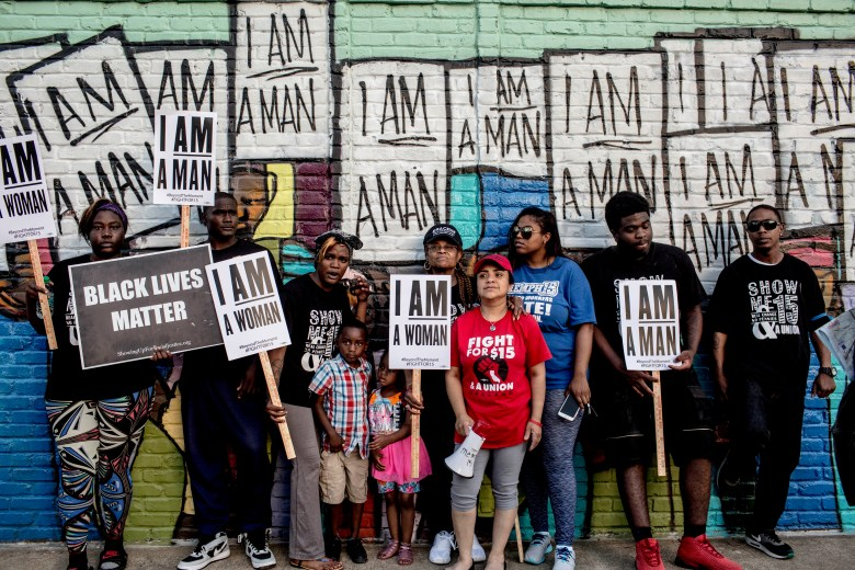 "A group of people holding ""I Am A Man"" signs stand in front of a mural commemorating the 1968 sanitation workers' strike that brought Dr. Martin Luther King Jr. to Memphis"