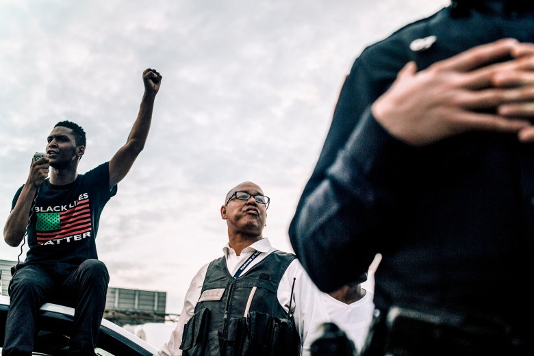 DeVante Hill sits atop a car while addressing a crowd of protestors. Memphis Police Department Director Michael Rallings looks on.