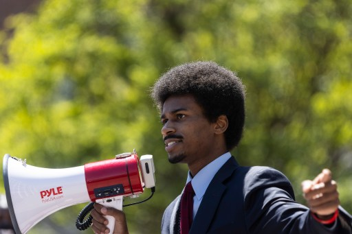 Portrait of Justin J. Pearson holding a megaphone at a rally.