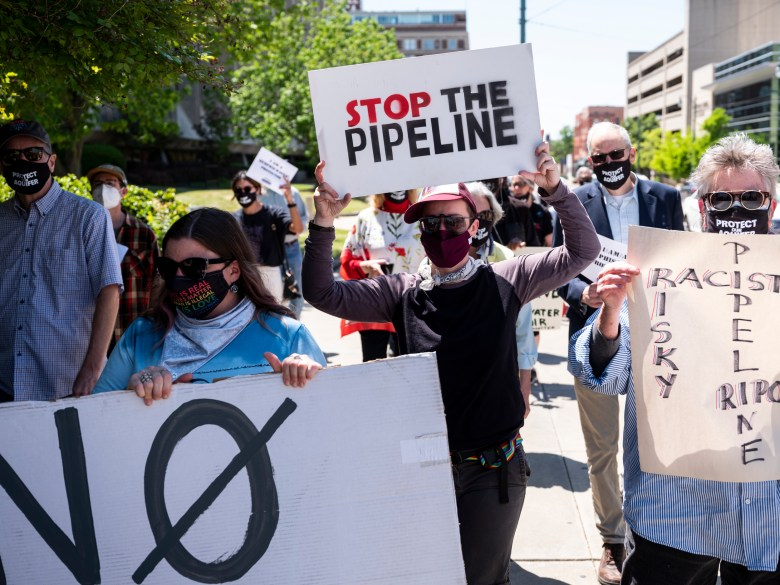 Masked Byhalia Pipeline protestors holding signs march from the National Civil Rights Museum in Memphis.