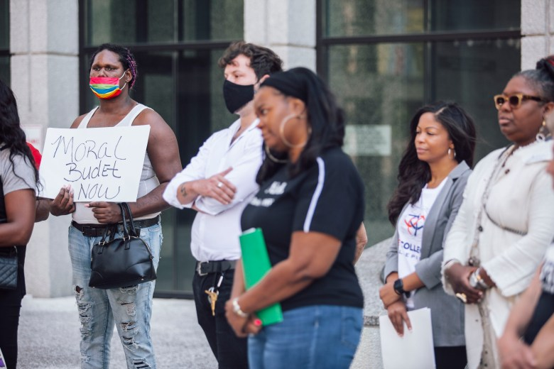 A group of people stand outside the Vasco A. Smith Jr. County Administration Building during a Memphis and Shelby County Moral Budget Coalition rally.