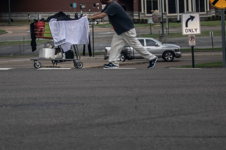 A man pushes a grocery cart containing personal items, including clothes and shoes, down a street in Memphis