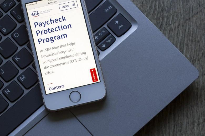 Stock photo of a cell phone sitting on top of a laptop. The cellphone screen shows an article about the Paycheck Protection Program (PPP).