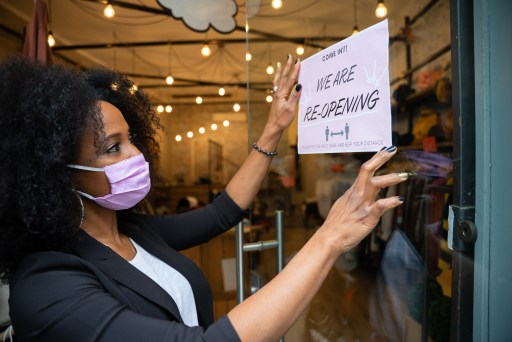 A stock photo of a Black woman posting a sign on a business door.