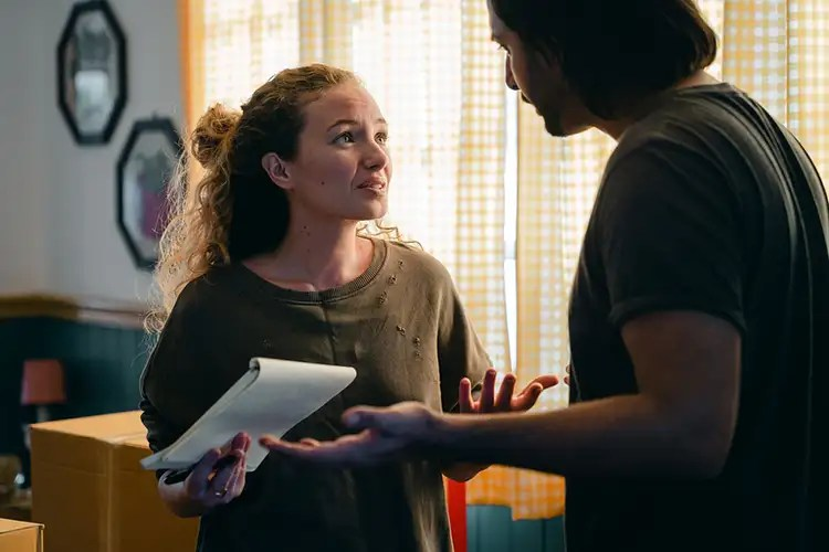 Image of a worried looking woman holding a notepad and talking with a man in their home to accompany justice gap text.