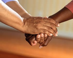 Close up photo of two people joining hands to accompany text regarding volunteer opportunities at the KCLL.