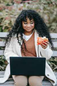 smiling black woman with burger using laptop on park bench