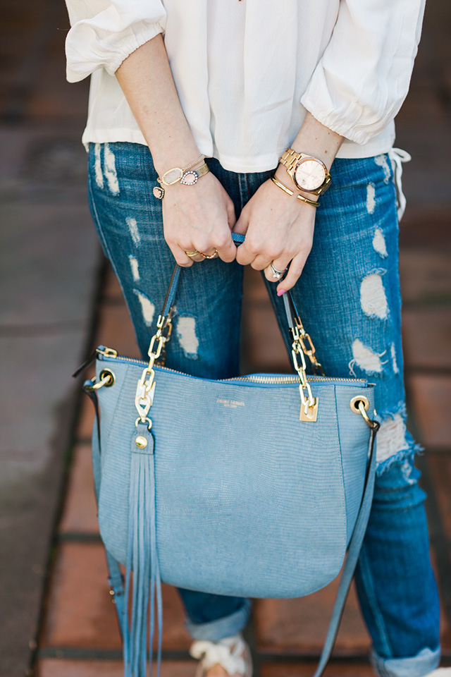 distressed jeans with a light blue bag with tassel detail