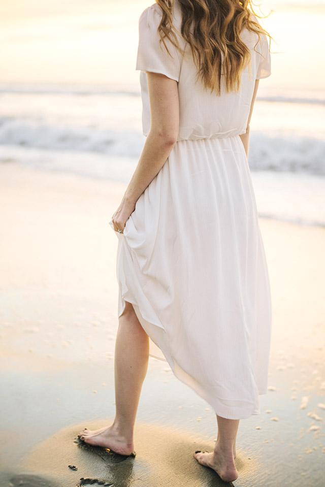 walking along the beach in a white flowy dress