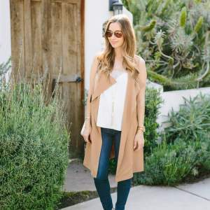 a neutral spring outfit with a sleeveless brown trench with white lace cami top and jeans