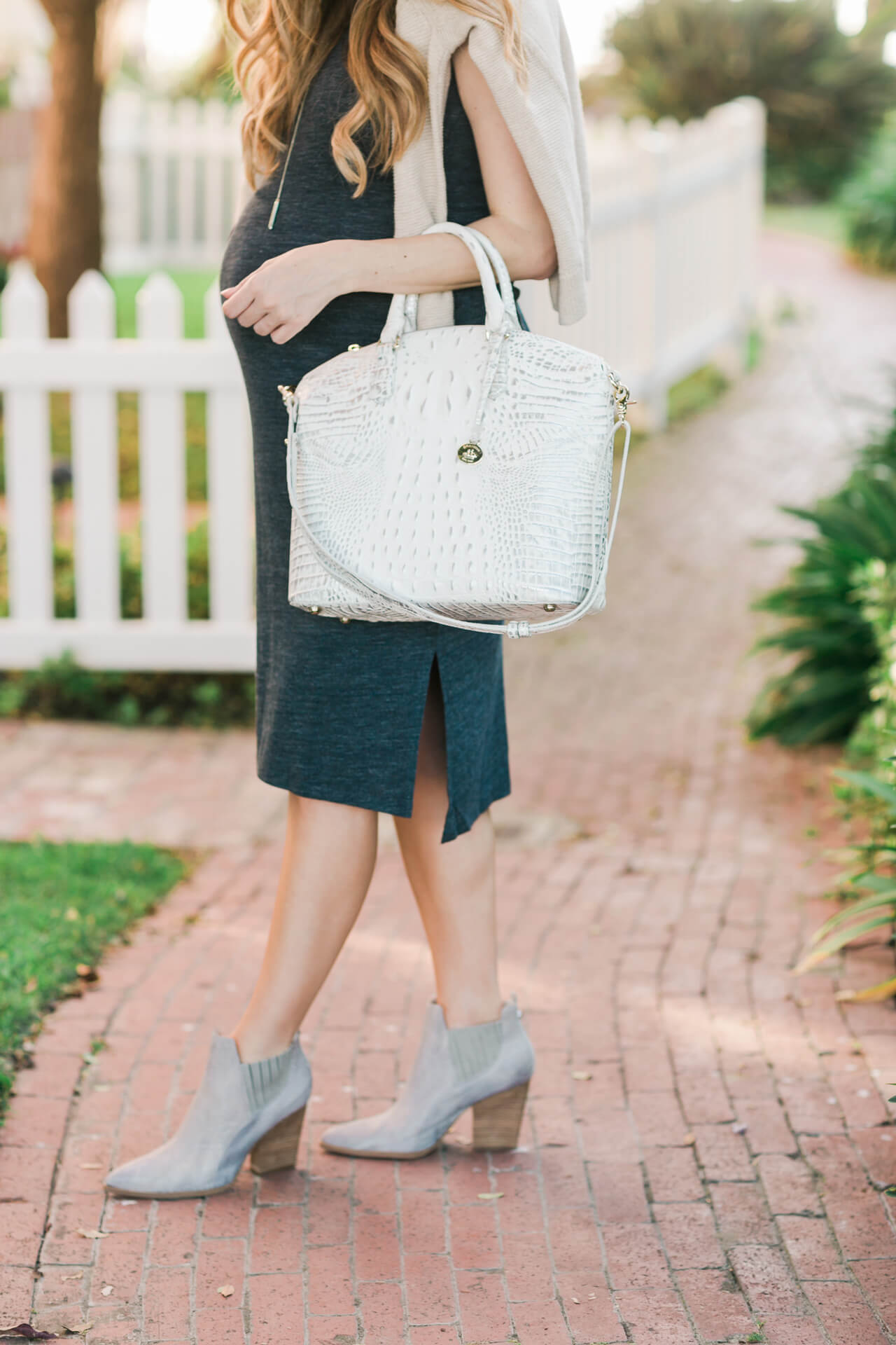 gray ankle booties with navy dress and white bag