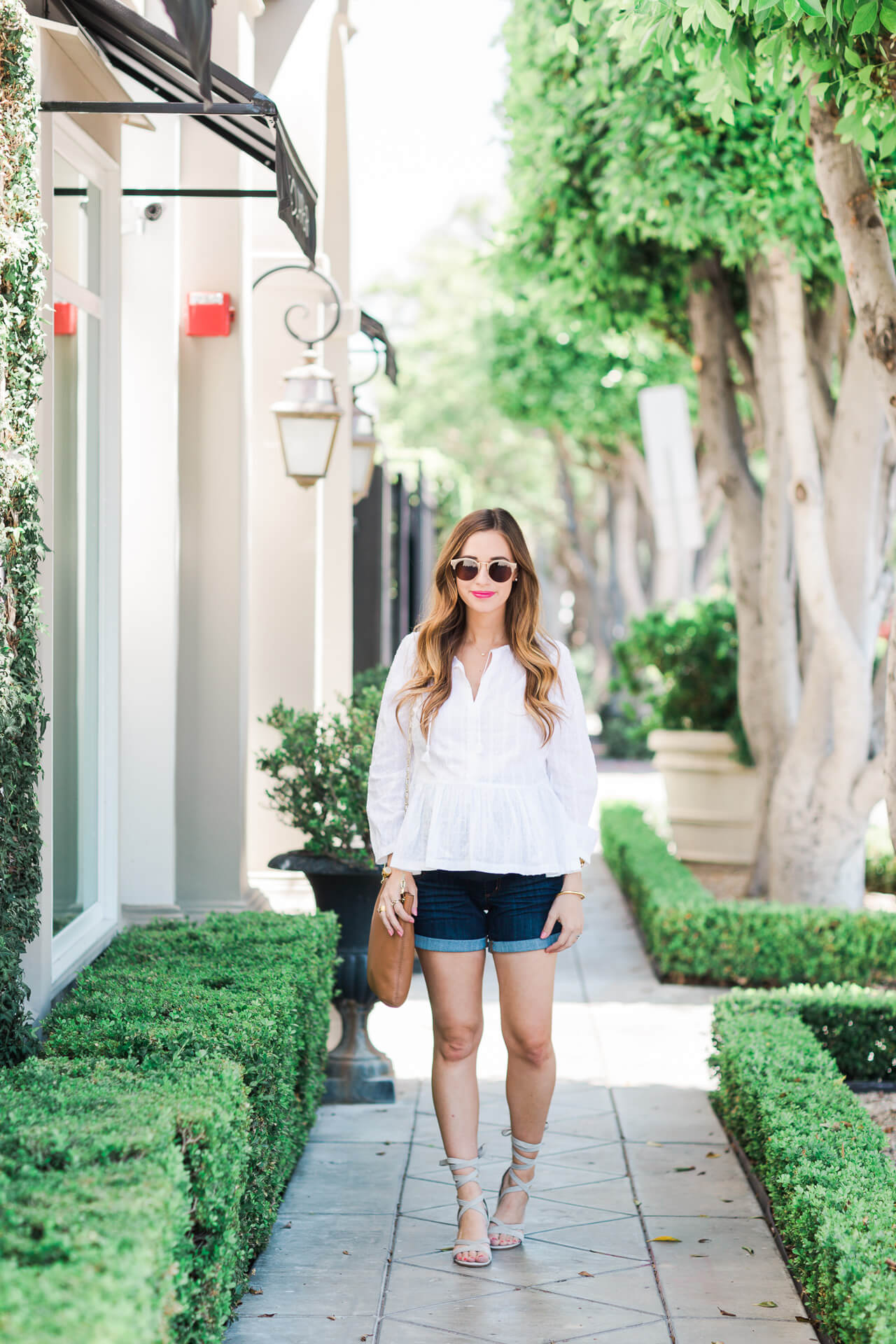 styling a white peplum top with denim shorts for summer