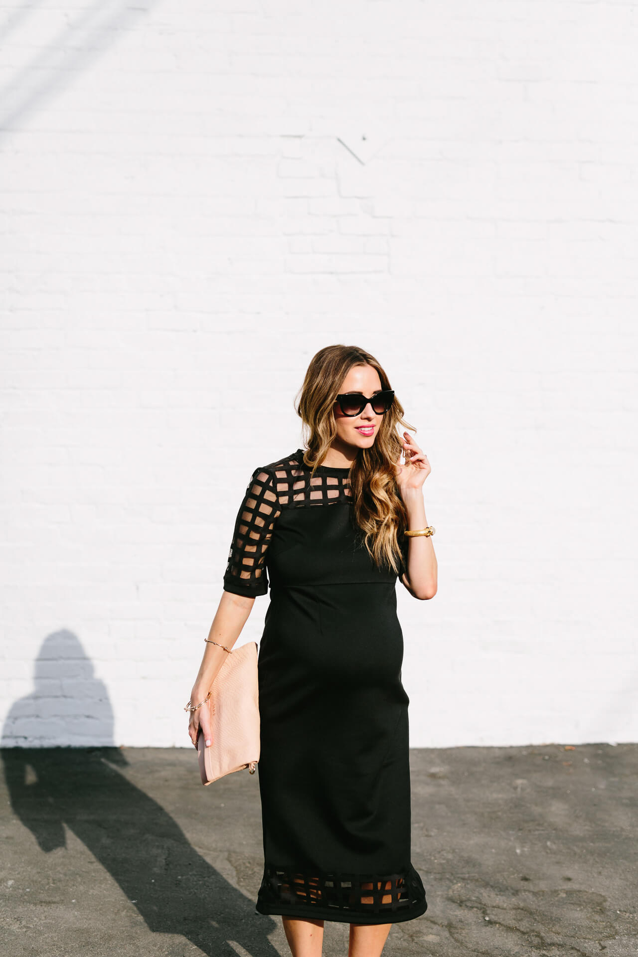 a black fitted dress with pink clutch