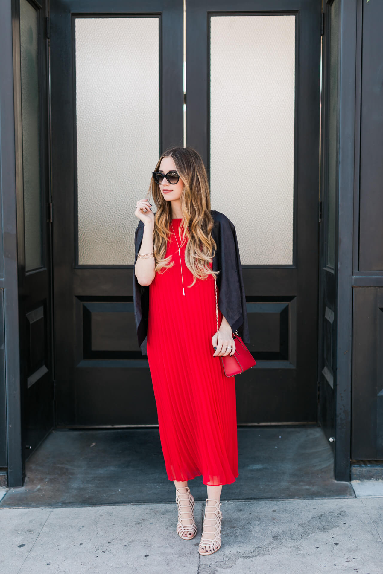 red pleated dress with black faux leather jacket