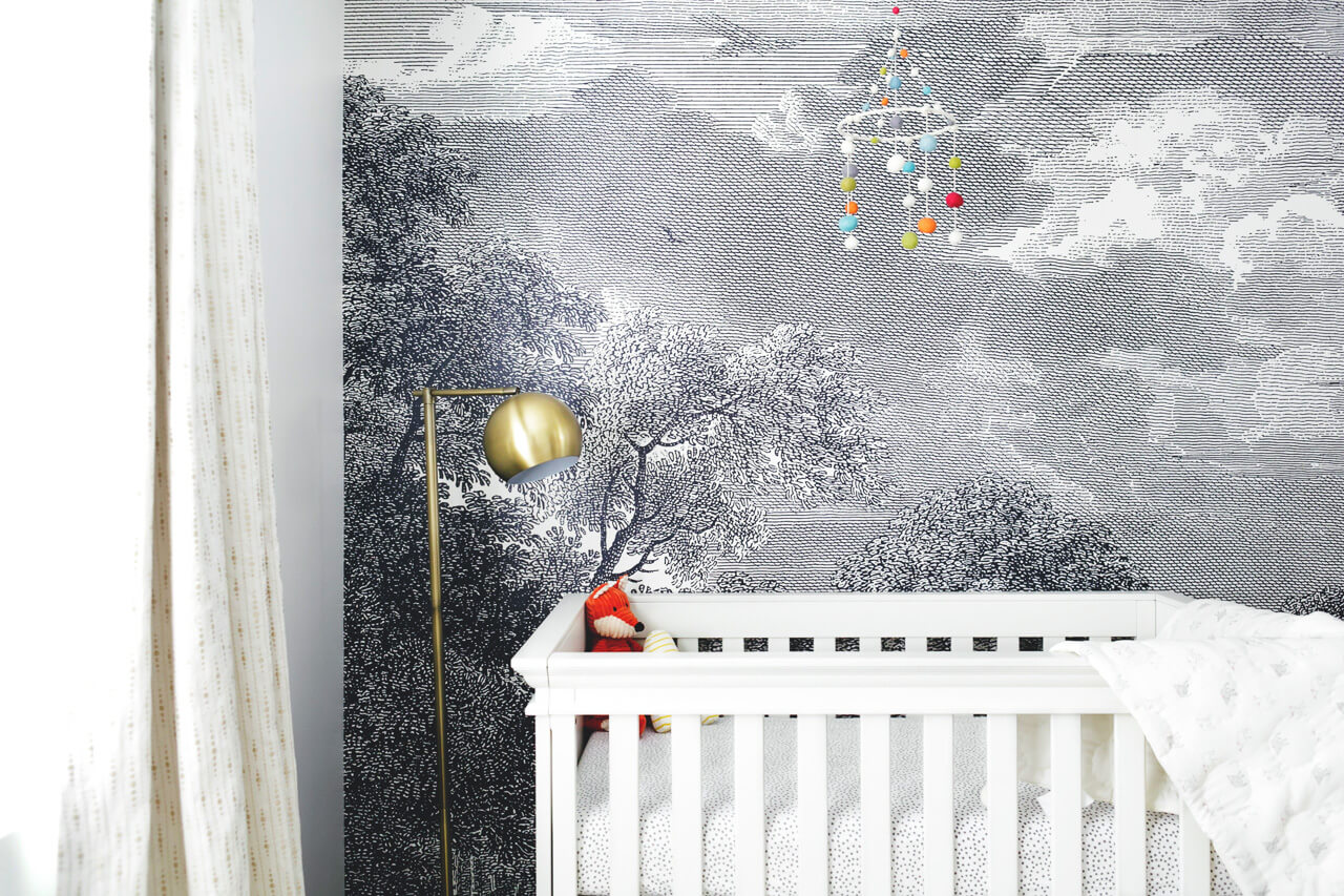 a white wooden crib with a tree mural wallpaper