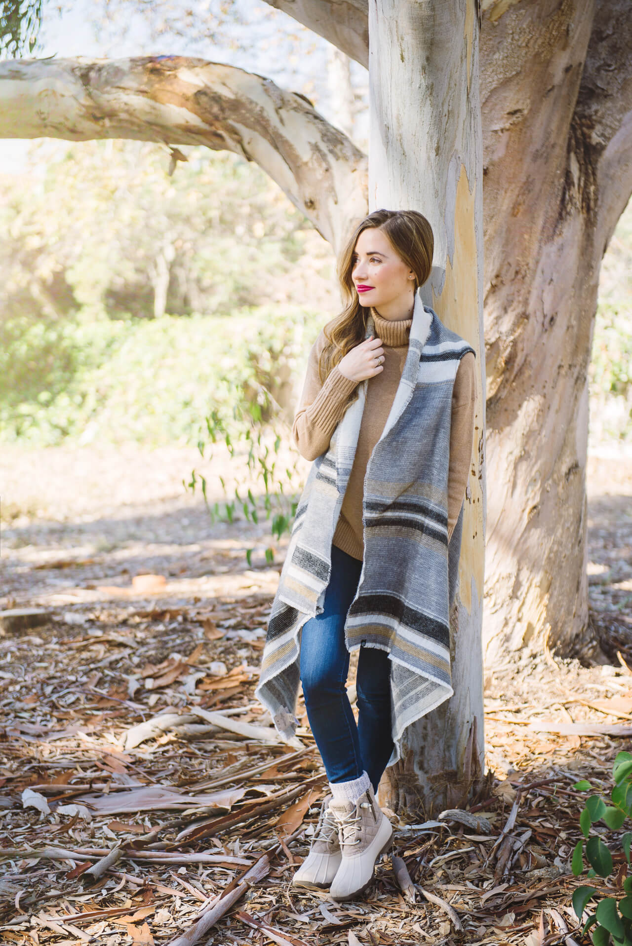 a striped poncho with duck boots