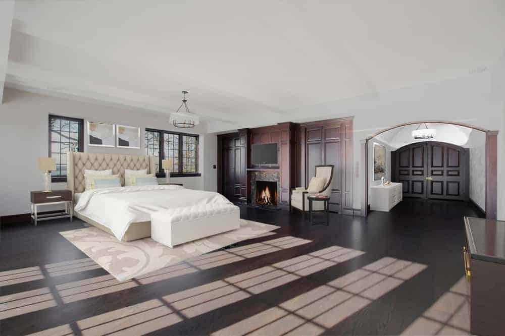 La chambre principale est spacieuse et son grand lit blanc. À côté, un mur lambrissé abrite la cheminée.©Toptenrealestatedeals.com