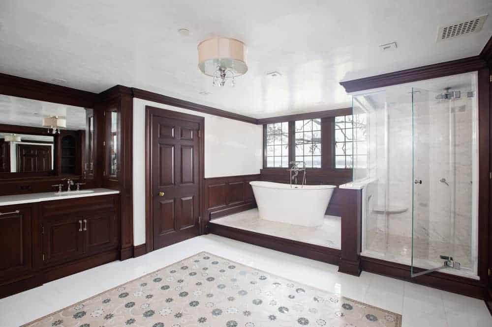Salle de bains principale, avec des tons beige et bois mettant en valeur la baignoire et la douche vitrée.©Toptenrealestatedeals.com
