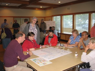 Attendees look at maps of the 42-acre park site during the June 11 open house at Ballinger Park.