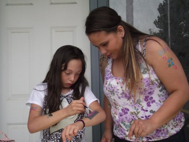 Faith Mushrow, age 10 of Everett, works on a butterfly glitter tattoo, watched by Lynnwood resident Theresa Cleven