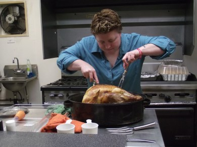 Crystal Thompson carves up the turkey for the Americorps dinner. Safeway, Albertsons and QFC all donated food for the event.