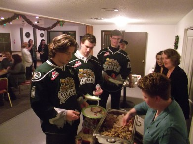 Americorps volunteers serve up members of the Everett Silvertips hockey team at the Wednesday night dinner.