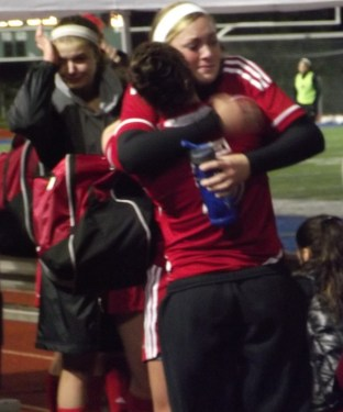 The Hawks' Maddy Kristjanson hugs Allison Lorraine following the game.