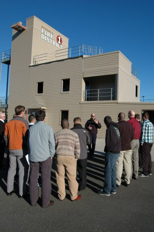 Snohomish County Fire District Captain John Chalfant leads a group of military veterans on a tour of the district's training tower during Operation Career Boost.