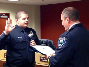 Reserve Police Officer Mike Ellis being sworn in by Police Chief Greg Wilson .