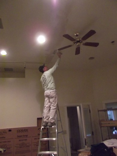 A volunteer does some finishing work on ceiling sheet rock.