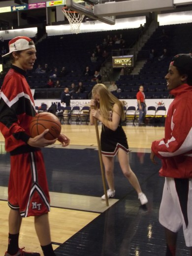 At halftime of the King Classic, MTHS students (from left) Jack Pierce, Marissa Mason and Peter Kidane take part in a challenge, to spin 10 times around a broomstick then run the length of the court and sink a lay-in.