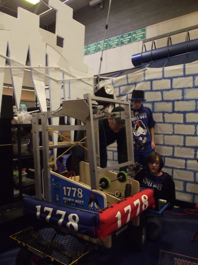 Chill Out! mentor Tom Borrud and team member (and son) Andrew Borrud (bottom right) make some repairs in the pit inbetween matches.