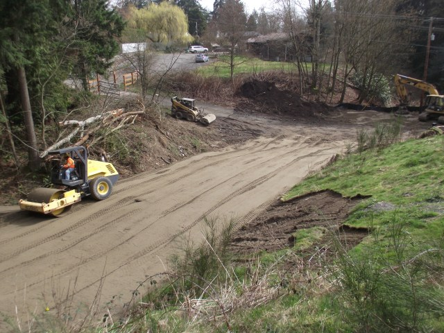 Work crews are busy utilizing some of the excess dirt excavated from the regional stormwater facility construction site in Mountlake Terrace to fill in a city service road that was badly needed of repairs. The service road, in the 22500 block of 52nd Avenue West and just east of the Mountlake Terrace dog park, is used by city public works, parks and property maintenance staff. Construction of the stormwater facility, located in front of the Mountlake Terrace Library at 23300-58th Avenue West, is expected to be completed this summer.