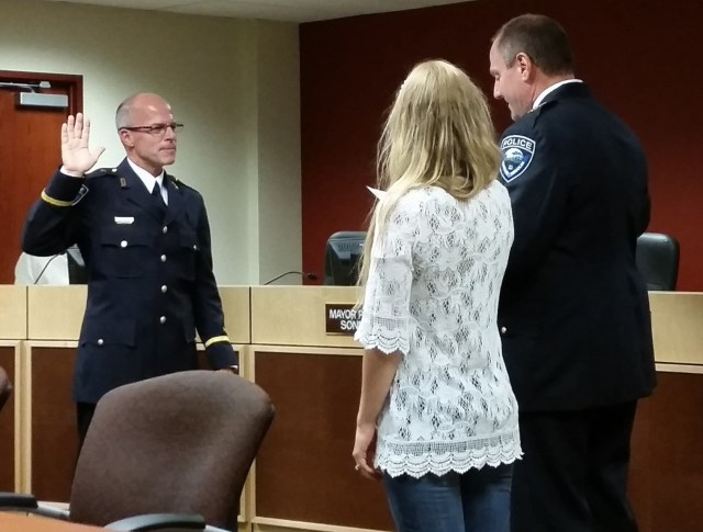 Commander Kevin Pickard sworn in by Police Chief Greg Wilson, as Commander Pickard's daughter looks on.