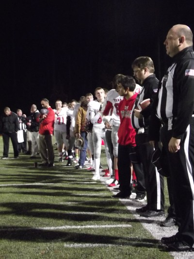 Game officials and the Mountlake Terrace Hawks football team observe a moment of silence before their game in Kingston Friday night to remember those affected by the shooting earlier in the day at Marysville-Pilchuck High School.