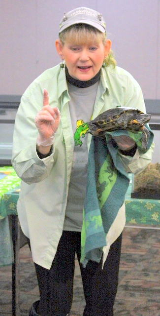 The Frog Lady holds a turtle.