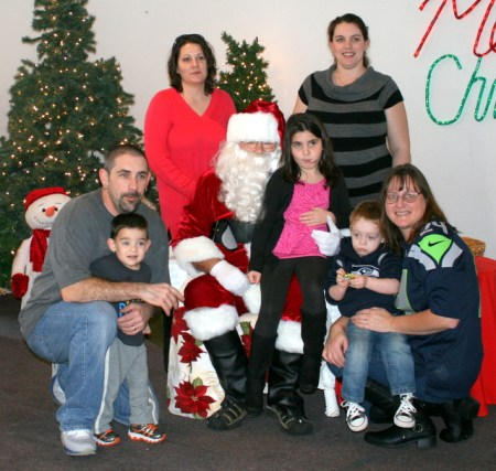 A family takes a photo with Santa Claus.