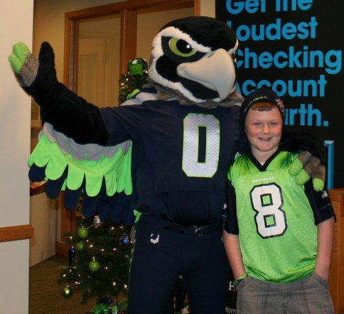 Cameron Simpson (right) poses with Seattle Seahawks mascot Blitz Friday at HomeStreet Bank in Mountlake Terrace. Blitz was helping to promote a toy drive for the Volunteers of America.