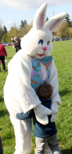 The Easter Bunny hugs a young child.