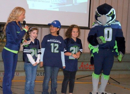 Seattle Seahawks cheerleader Tamaria Favell (left) asks Mountlake Terrace Elementary students Kayla Grabinski, Linah Khayal, and Arrika Lozano answer nutrition questions during a Fuel Up to Play 60 assembly Friday morning at Mountlake Terrace Elementary School. Seahawks mascot Blitz (right) also was part of the educational fitness and nutrition that encouraged students to get 60 minutes of exercise/activities a day and to eat healthy foods. The program was sponsored by the Washington State Dairy Council and the Seattle Seahawks. (Photos by David Pan)