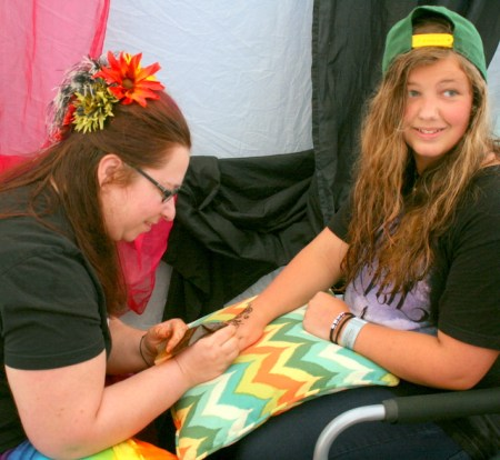 Antoinette Hippe of Magic Magpie Studio works on a Henna art design for Emerald Montgomery (right) of Edmonds during Tour de Terrace on Sunday. (Photos by David Pan)