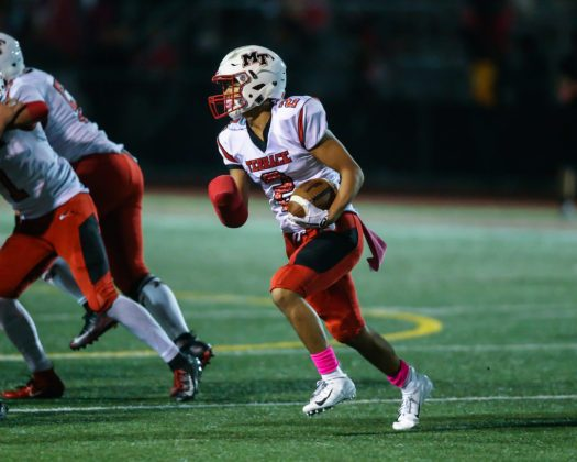 Dom Latham runs the ball with his right hand wrapped up from breaking it in the previous game