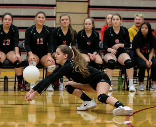 The Hawks' bench watches as Isabel Ong digs out a ball.