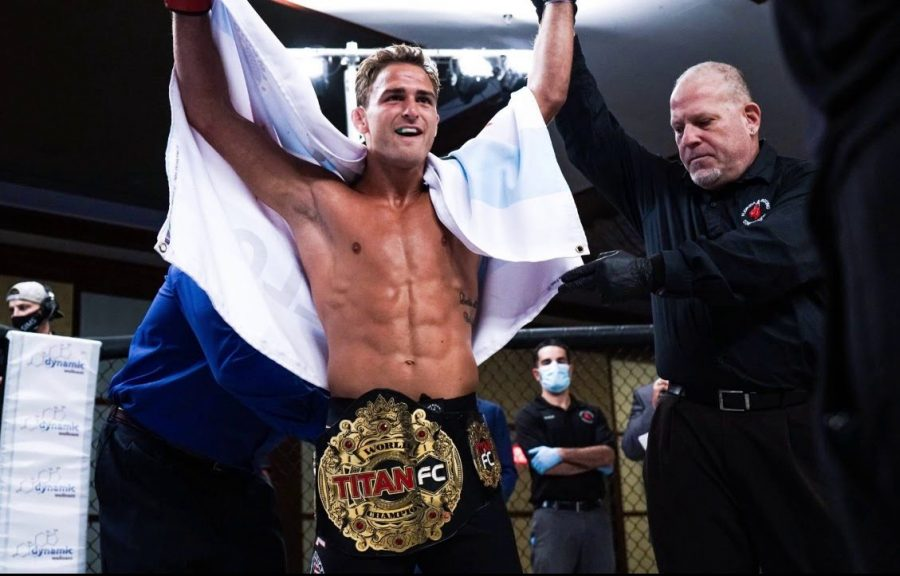 Danny Sabatello raises his arms after getting the Titan FC belt put on him.