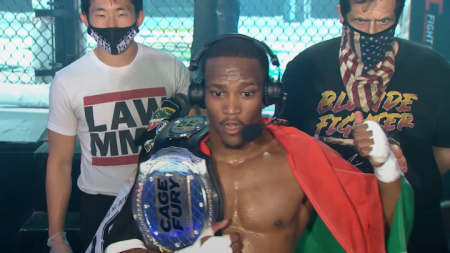 Phumi Nkuta holds his CFFC belt with the flag of South Africa wrapped around him. He has a headset on and is pointing behind him to the CFFC cage.