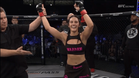 Cheyanne Buys gets her arm raised in the LFA cage